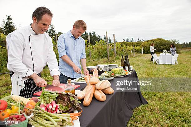 men preparing food for dinner party in field - farm to table stock photos and pictures