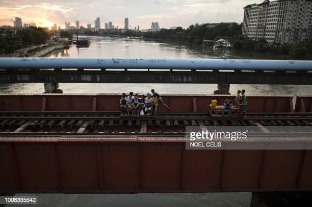 Men propel passengers in footpowered trolleys along a railroad track in Manila on July 31 2018 Locally referred as just the trolley it gives locals a...