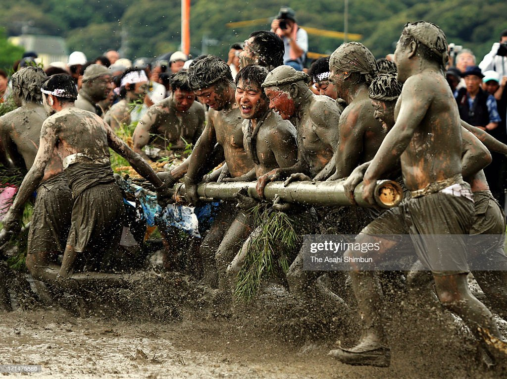 Men pull a bamboo each other in a puddy during the 'Otaue Shiki' ritual to pray for a good harvest at Izawanomiya Shrine on June 24, 2013 in Shima, Mie, Japan. The festival dates back in 12th century.