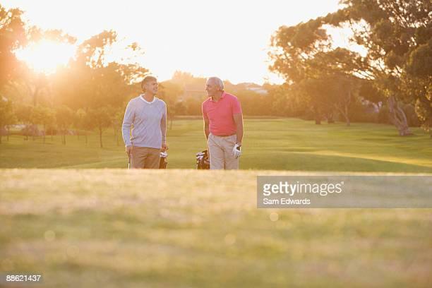 Männer ziehen Golfwagen auf den Golfplatz