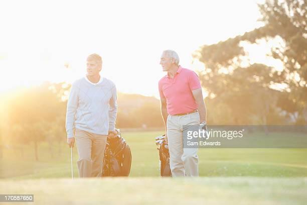 Herren ziehen Golfwagen