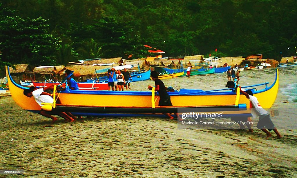 Men Pulling Longtail Boat At Beach Against Trees : Stock Photo