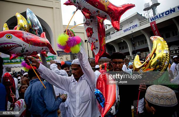 Men purchase balloons outside the National Mosque Baitul Mukarram during Eid alFitr on July 29 2014 in Dhaka Bangladesh Muslims around the world are...