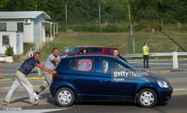 men pushing a broken-down compact car near the serbian border, serbia, europe - men stockfoto's en -beelden