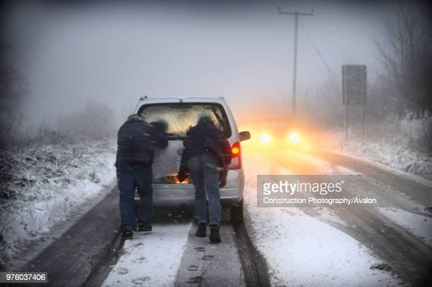 Men pushing car stuck on snowy road UK