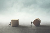 men pushing different geometric wooden shapes