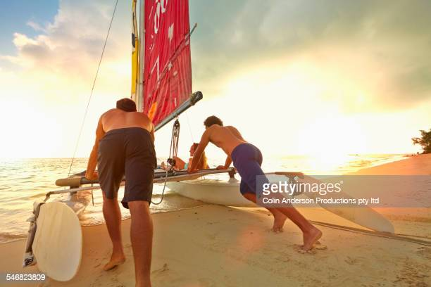 men pushing sailboat into ocean from beach - catamaran stock photos and pictures