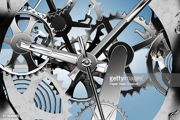 Men pushing the inside silver cogs of a clock
