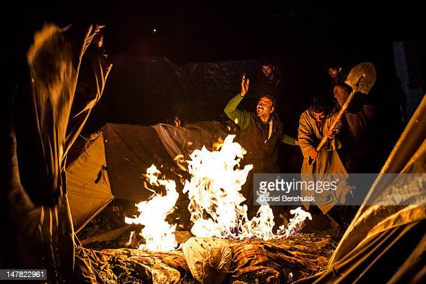 Men put out a fire after some kerosene spilled onto a tent at a campsite near to the Amarnath Cave one of the most revered Hindu shrines on June 29...