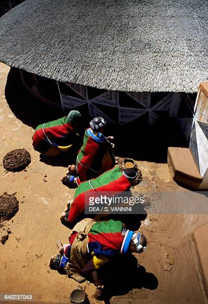 Men putting down flooring in front of a rondavel in a Ndebele village South Africa