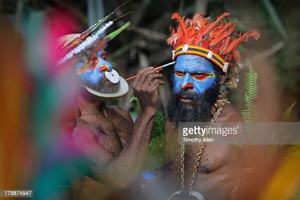 Men putting on face paint for festival
