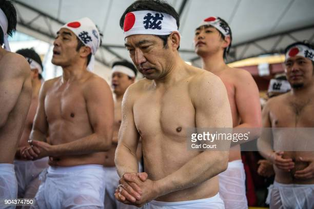 Men queue to reenter a pool as they take part in a purification ritual that involves pouring icecold water over themselves at Kanda Myojin shrine on...
