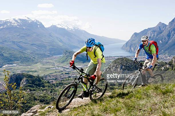 Men racing electic-mountainbikes cliff valley