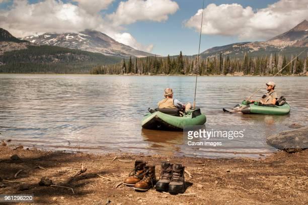 Men rafting on lake against mountains