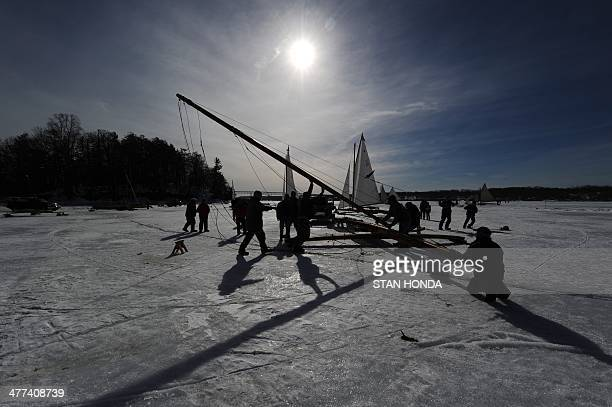Men raise the main mast on an ice boat before it sails on a frozen Hudson River March 7 2014 in Barrytown New York These historic 'ice yachts' some...