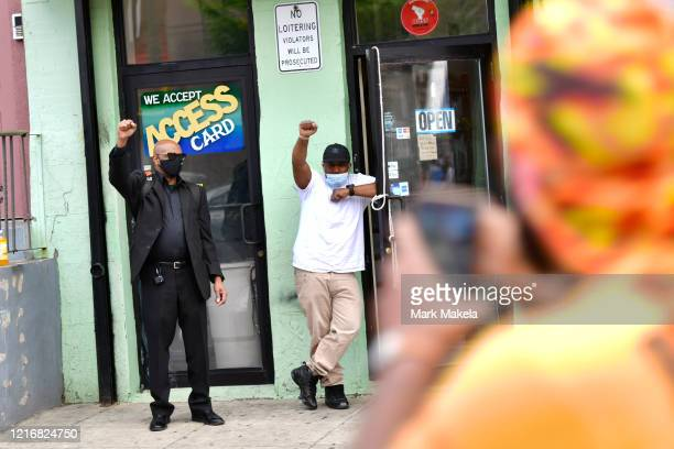 Men raise their arms in solidarity with protesters marching after widespread unrest following the death of George Floyd on June 1 2020 in...