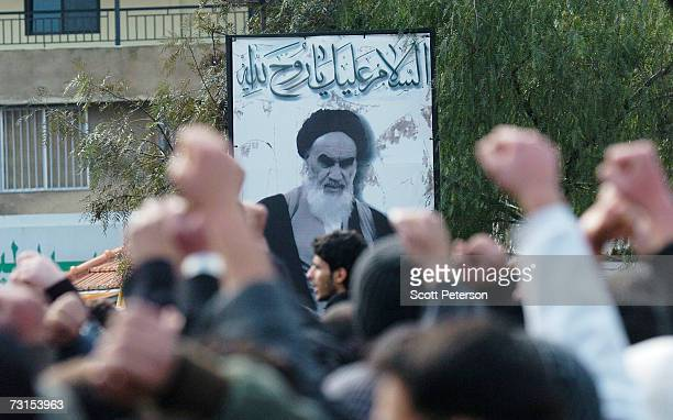 Men raise their fists in the air as they pass a portrait of Iran's revolutionary leader Ayatollah Khomeini as Shiite Muslims loyal to the Hizbullah...