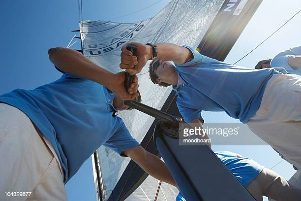 men raising sail on yacht, view from below - segeln stock-fotos und bilder