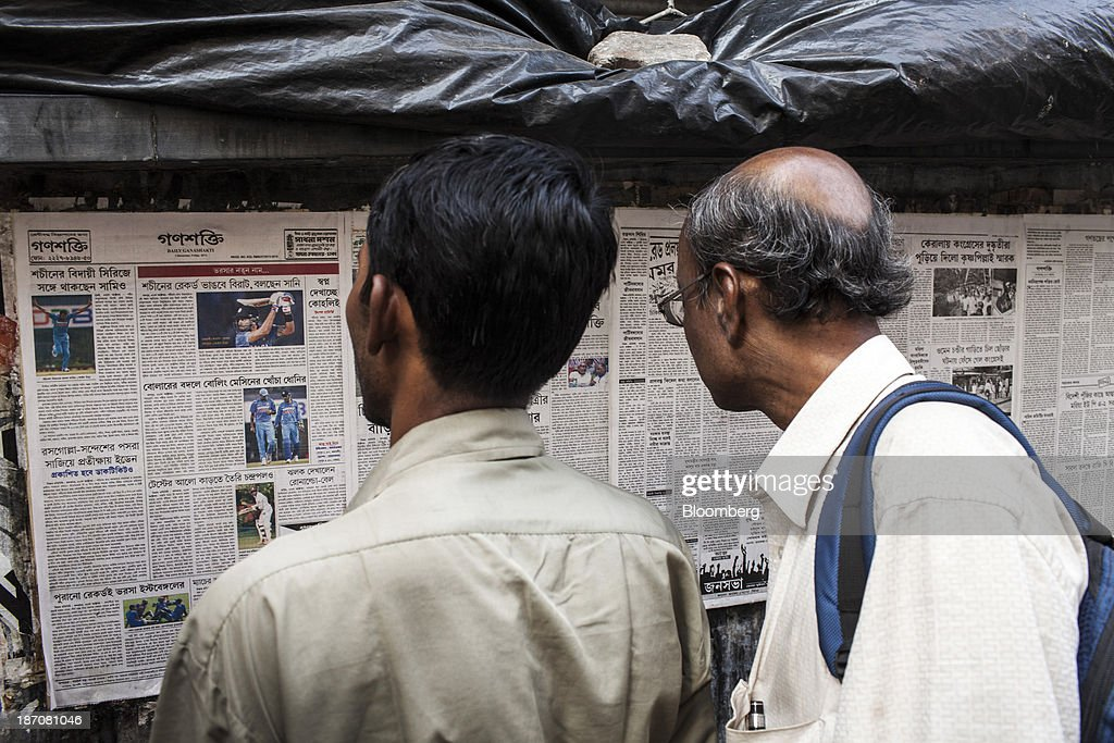 Men read a newspaper on a notice board in the BBD Bagh area of Kolkata, West Bengal, India, on Friday, Nov. 1, 2013. Indian stocks fell for the first time in six days, led by technology and consumer companies, after benchmark indexes climbed to records in a holiday trading session on Nov. 3. Photographer: Sanjit Das/Bloomberg via Getty Images