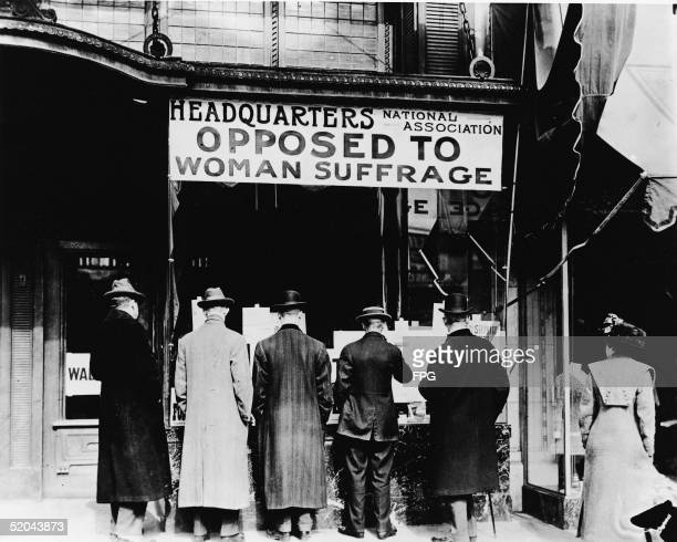 Men read literature posted in the window of the headquarters of the National Association Opposed to Woman Suffrage as woman stands off to the side...