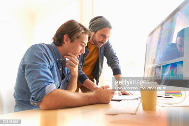 Men reading clipboard near computer in office