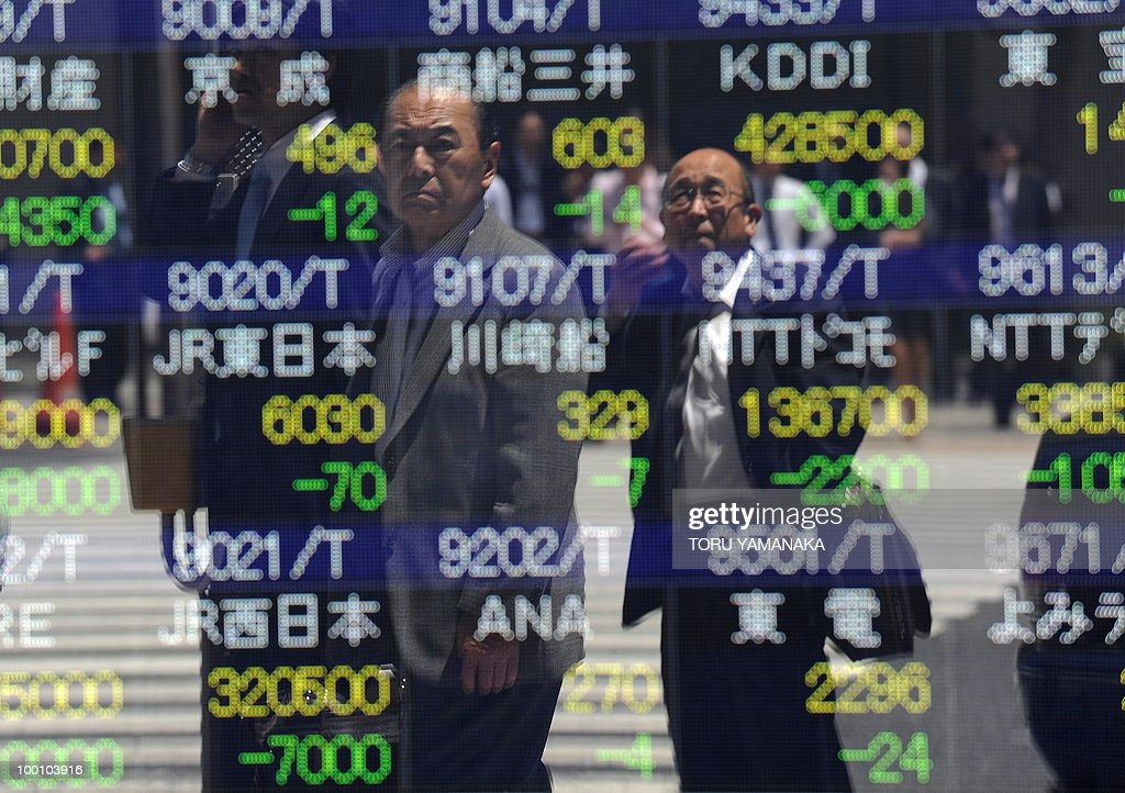 Men reflect on an electric quotation board flashing share prices of the Tokyo Stock Exchange (TSE) in front of a securities company in Tokyo on May 21, 2010. Japanese shares plunged 2.51 percent by noon following Wall Street's biggest drop in more than a year and as the continued strength of the yen prompted investors to sell shares. AFP PHOTO/Toru YAMANAKA