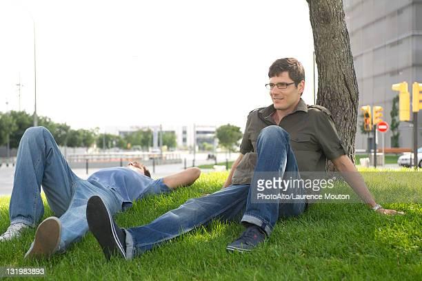 Men relaxing in grass in city
