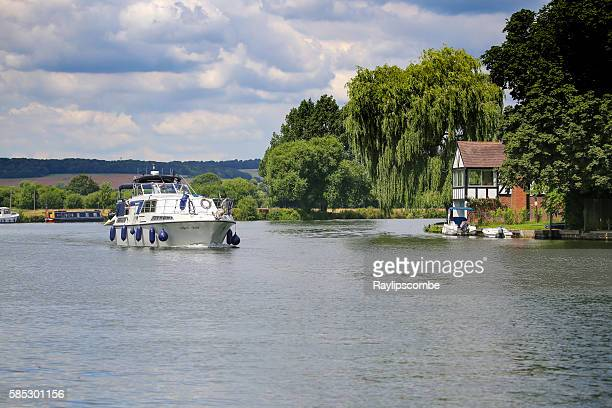 2 men relaxing on a motorboat, cruising along the Thames