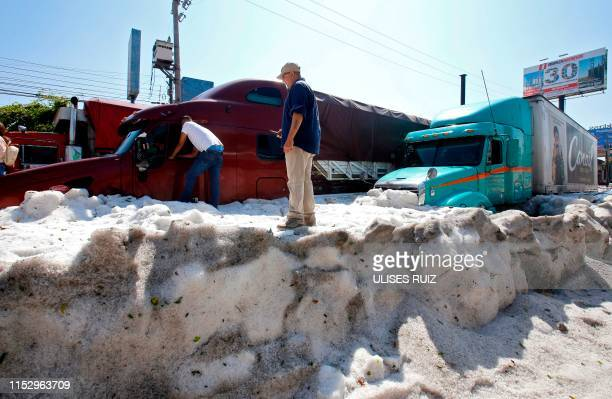 Men remain next to trucks buried in hail in the eastern area of Guadalajara, Jalisco state, Mexico, on June 30, 2019. - The accumulation of hail in...
