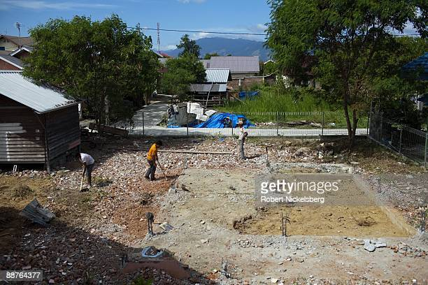 Men remove rubble from a destroyed house in a Banda Aceh neighborhood devastated by the December 26 2004 tsunami disaster in Aceh province's capital...