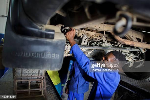 Men repairing a car in an auto repair shop on September 29 2015 in Beira Mozambique