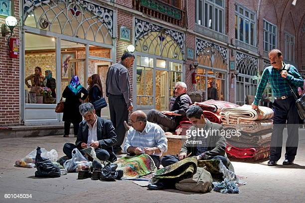 Men repairing carpets in the old historic bazaar of the city Tabriz, East Azerbaijan, Iran.