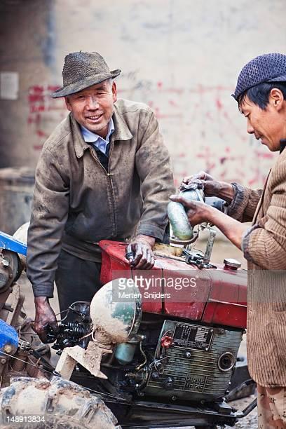 men repairing tractor. - merten snijders stockfoto's en -beelden