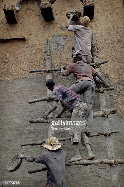 men replaster the great mud mosque, djenne, mali - djenne grand mosque stock pictures, royalty-free photos & images