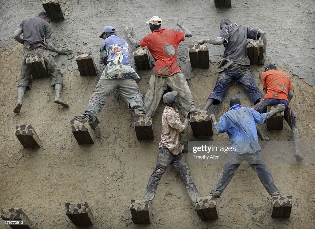 Men replaster the great mud Mosque, Djenne, Mali : Stock Photo