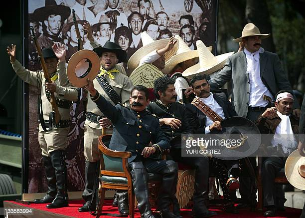 Men representing Mexican revolutionary leaders Francisco Villa and Emiliano Zapata perform during a military parade commemorating the 101th...