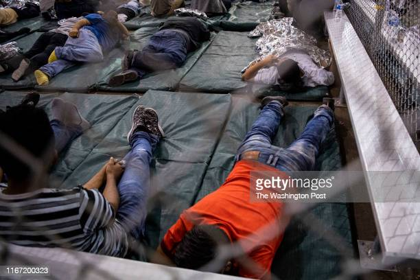 Men rest on bed pads in the US Border Patrol Central Processing Center in McAllen, Texas on August 12, 2019. Border Patrol officials said that 1,267...