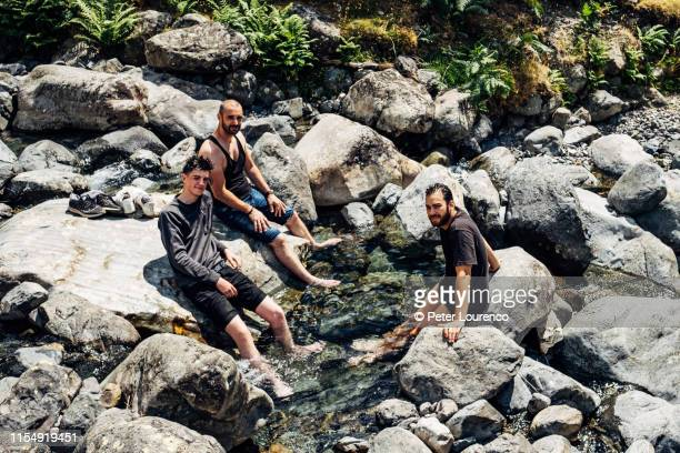 3 men resting feet in mountain stream - peter lourenco stock pictures, royalty-free photos & images