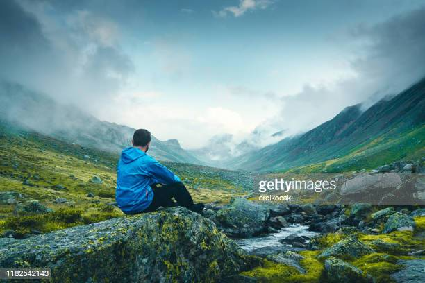 men resting on the rock - one man only stock pictures, royalty-free photos & images