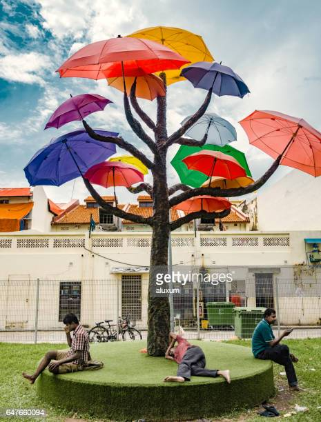 Men resting under umbrella trees in little India Singapore