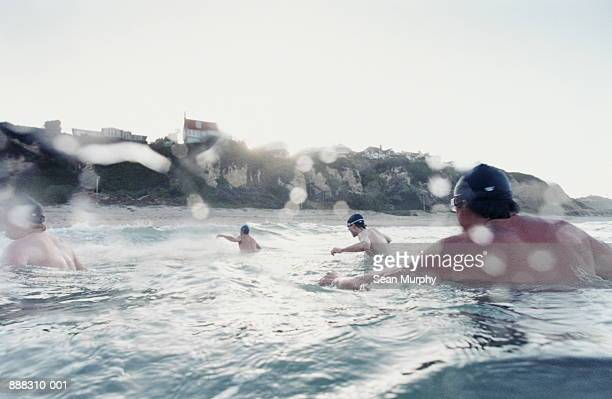 men returning to shore after swim - sea swimming stock pictures, royalty-free photos & images