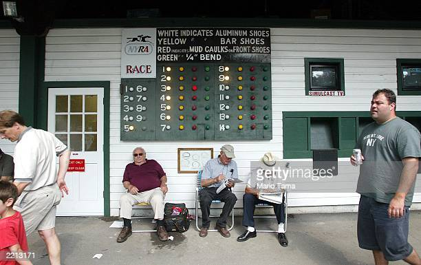 Men review tip sheets at Saratoga Race Course during opening weekend of the thoroughbred racing season July 26 2003 in Saratoga Springs New York The...