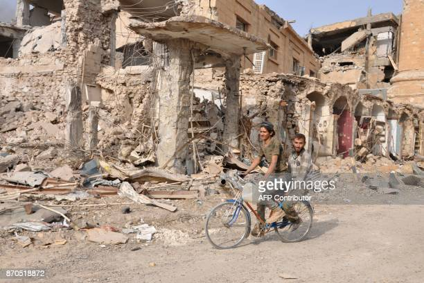 TOPSHOT Men ride a bicycle in the eastern Syrian city of Deir Ezzor during a military operation by government forces against Islamic State group...