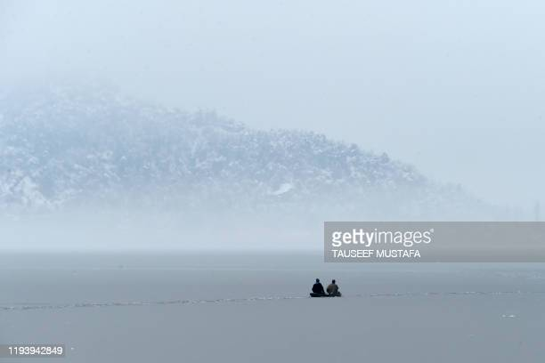 TOPSHOT Men ride a boat near a frozen portion of Dal lake after a heavy snowfall in Srinagar on January 16 2020
