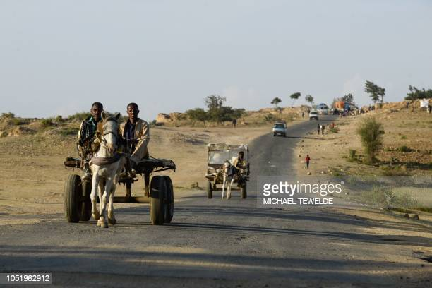 Men ride a donkey cart walk through a road on the Ethiopian side of the EthiopiaEritrea border on October 3 2018 The whirlwind peace process between...