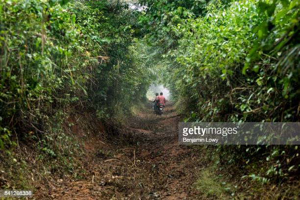 Men ride a motorbike near a small secluded farming commune near Abengourou Ivory Coast