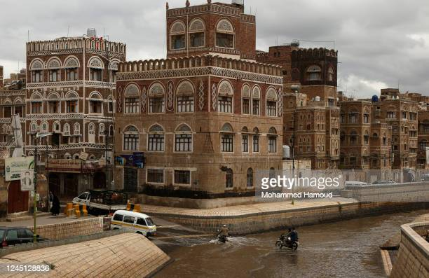 Men ride bikes in flooded waters near historical buildings of the old quarter of Sana'a on June 04 2020 in Sana'a Yemen