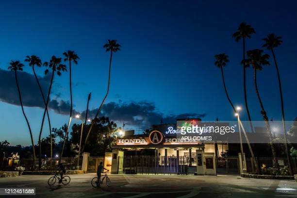 Men ride bikes in front of The Rose Bowl Stadium in Pasadena, California, on May 9 during the novel coronavirus pandemic. - Events that involve mass...