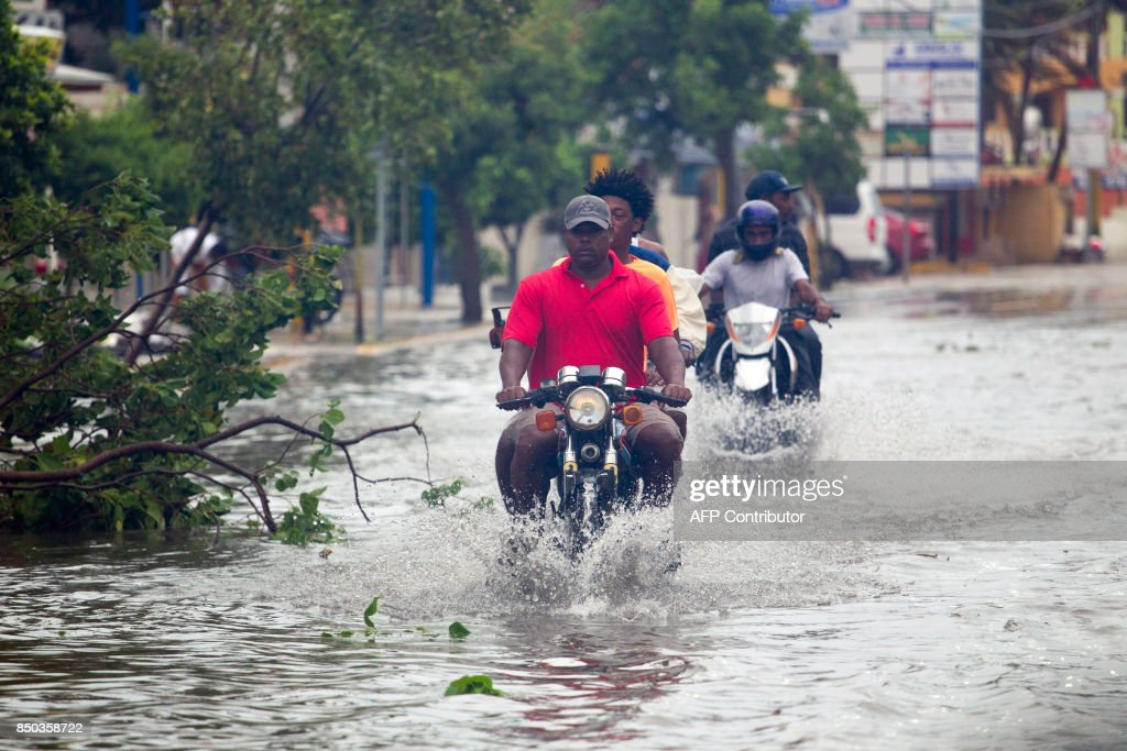 Men ride motorcyles along a flooded street in Punta Cana, in the Dominican Republic, as Hurricane Maria approaches on September 20, 2017. The government of the Dominican Republic told people to stay home from their public and private sector jobs on Thursday, when the hurricane is expected to hit the island. / AFP PHOTO / Erika SANTELICES
