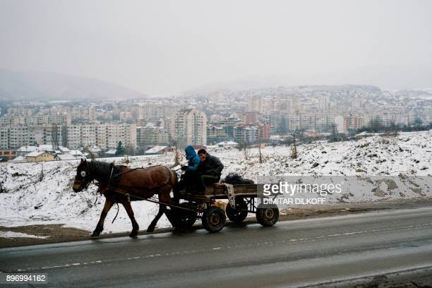Men ride on a horse cart in the predominantlyRoma suburb of Fakulteta on the outskirts of Sofia on December 20 2017 Bulgaria's capital Sofia is...